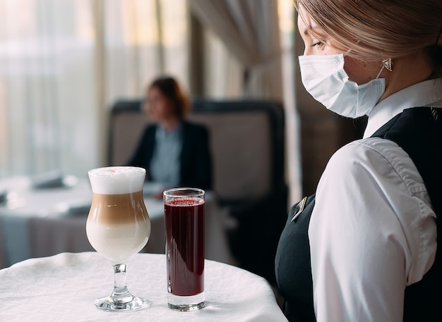 Serveuse d'apparence européenne dans un masque médical sert du café au lait.