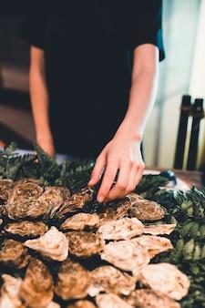 Serveuse arrangeant une assiette d'huîtres