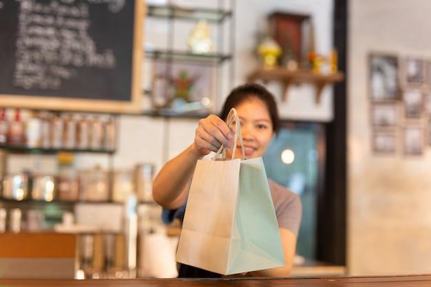 Serveuse au comptoir donnant un sac en papier écologique avec boissons à emporter au café