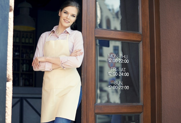 Serveuse avec les bras croisés devant les portes du café