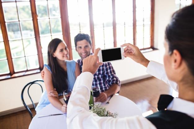 Serveuse en cliquant sur la photo d'un couple au restaurant