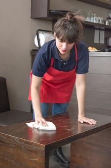 Serveuse essuyant la table avec une serviette dans le caf�