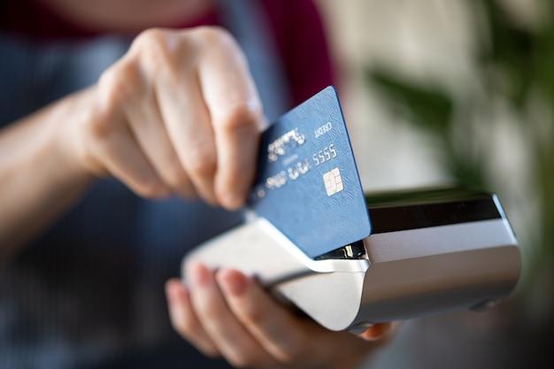 Serveuse glissant la carte de crédit sur pos
