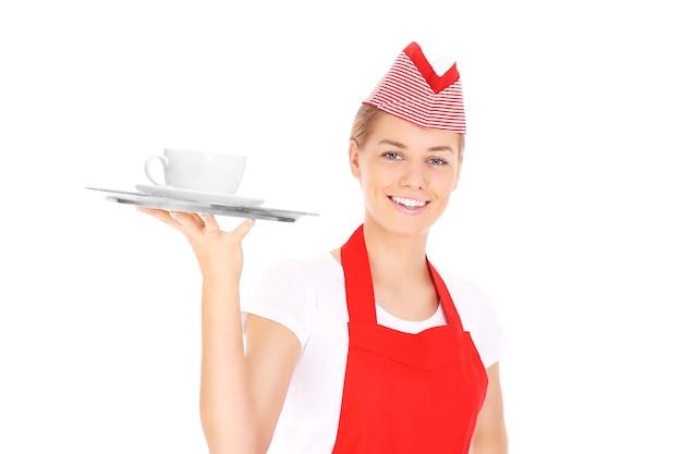 Une serveuse heureuse posant avec un plateau de service et du café sur fond blanc