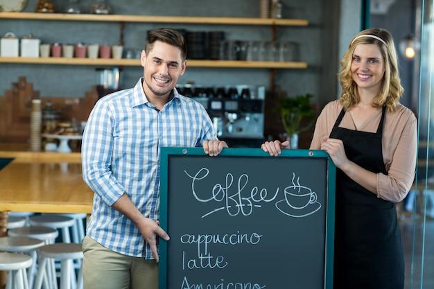 Serveuse et homme debout avec tableau de menu au café