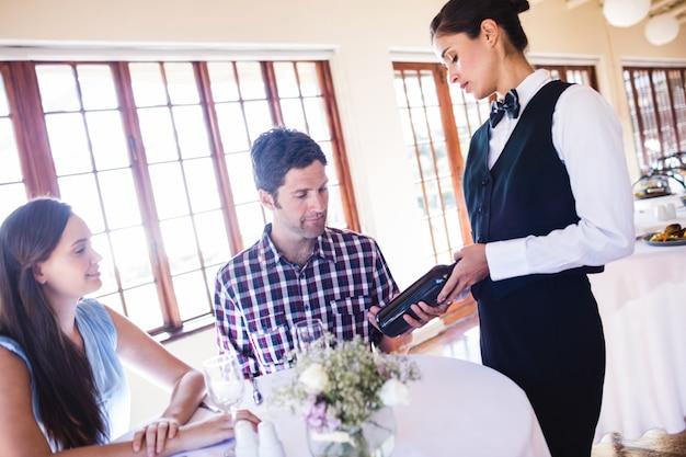 Serveuse montrant le vin au client à la table