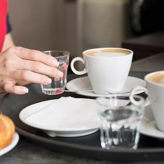 Serveuse en plaçant un verre d'eau avec du café dans le plateau