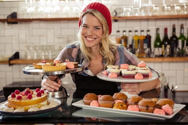Serveuse posant avec des gâteaux