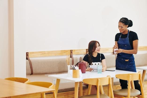 Serveuse positive parlant à une cliente et notant sa commande