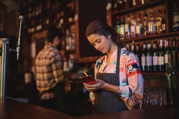 Serveuse prenant une commande sur le bloc-notes au comptoir