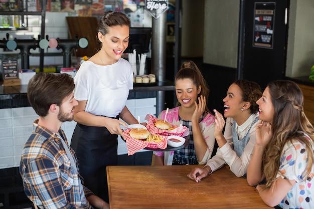 Serveuse servant des hamburgers aux clients du restaurant