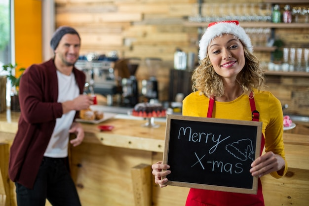 Serveuse souriante debout avec merry x mas sign board in cafe
