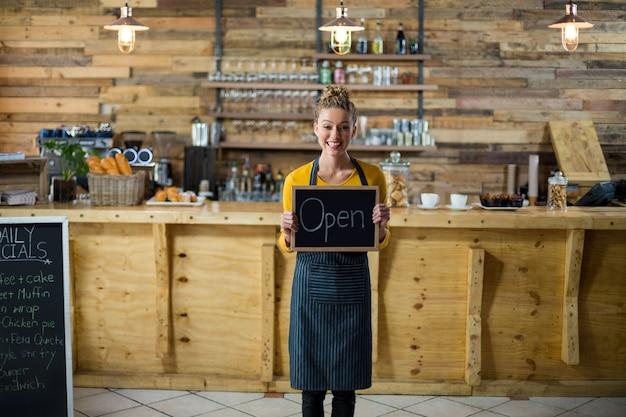 Serveuse souriante debout avec panneau ouvert au café