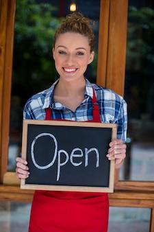 Serveuse souriante debout avec panneau ouvert à l'extérieur du café