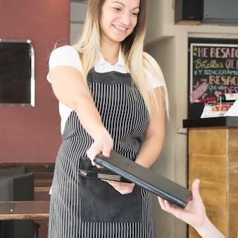 Serveuse souriante donnant le menu au client dans le restaurant