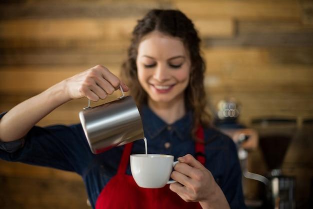 Serveuse souriante faisant une tasse de café