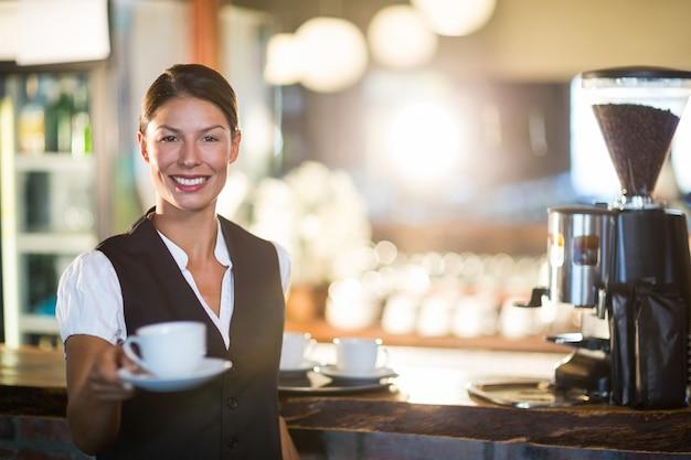 Serveuse souriante servant une tasse de café