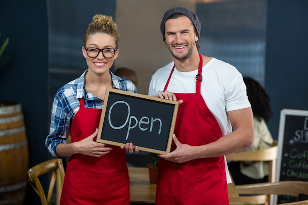 Serveuse souriante et serveur debout avec panneau ouvert dans le café