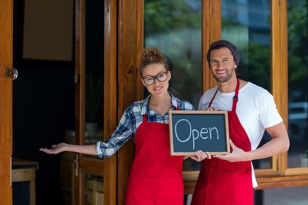 Serveuse souriante et serveur debout avec panneau ouvert à l'extérieur du café