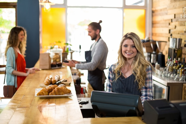 Serveuse souriante et serveur travaillant au comptoir