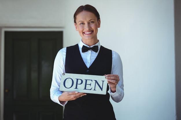 Serveuse souriante tenant une pancarte ouverte