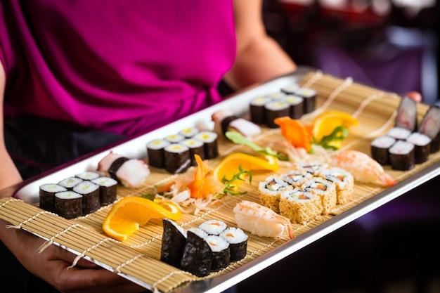 Serveuse avec sushi au restaurant asiatique
