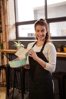 Serveuse tenant des boîtes avec un gâteau à l'intérieur