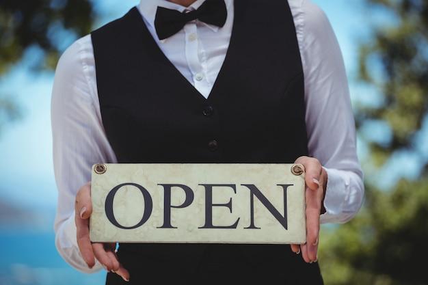 Serveuse tenant une pancarte ouverte