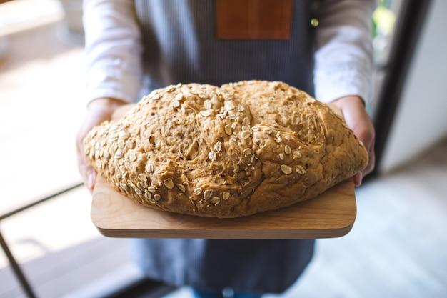 Une serveuse tenant et servant une miche de pain de grains entiers