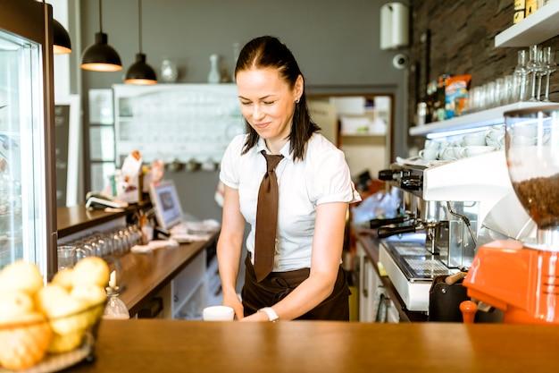 Serveuse en train de faire du café