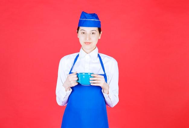 Serveuse en uniforme debout et tenant une tasse bleue sur le mur rouge.