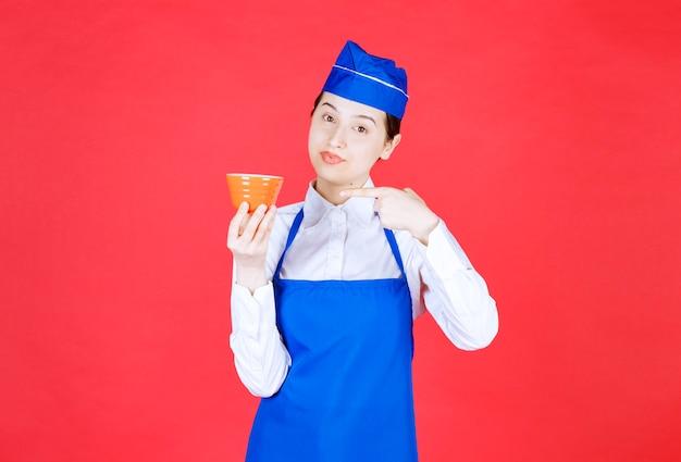 Serveuse en uniforme pointant vers un bol orange sur mur rouge.