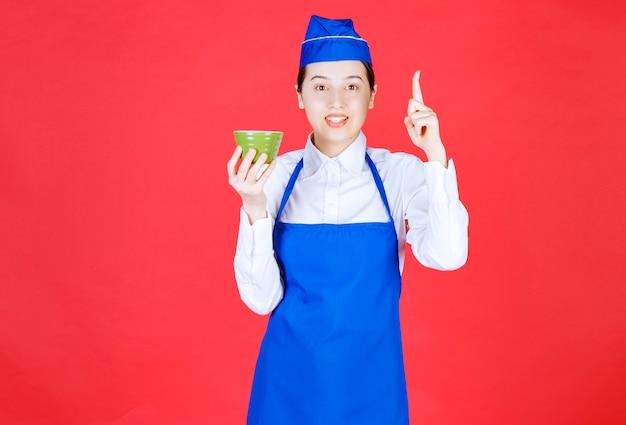 Serveuse en uniforme tenant un bol vert et pointant vers le haut avec le doigt.
