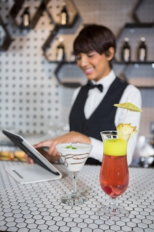 Serveuse, utilisation, tablette numérique, à, verre cocktail, dans, bar, compteur