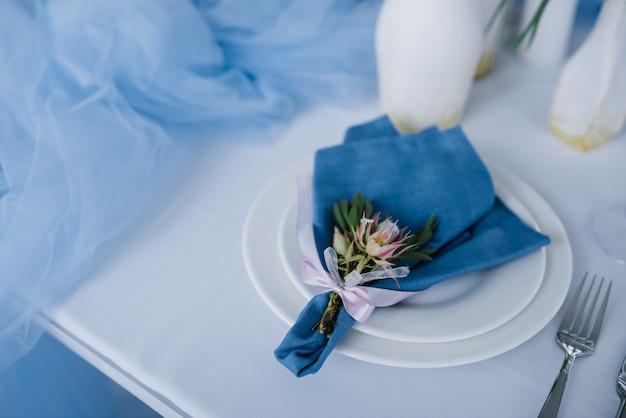 Servi pour la table de banquet de mariage en bleu blanc. décoration de mariage. serviette bleue avec fleur sur une plaque blanche.