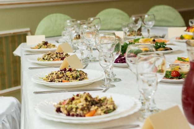 Servi pour une table de banquet. verres à vin avec serviettes, verres et salades.