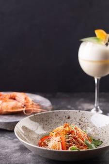 Servi à table au restaurant. salade funchoza aux crevettes et légumes aux graines de sésame, grosses crevettes corail et verre à cocktail.