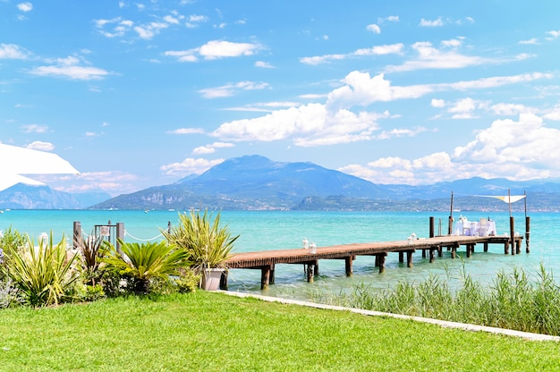 Servi à table pour un mariage au bord du lac. l'eau profonde, les montagnes et le ciel. journée romantique.