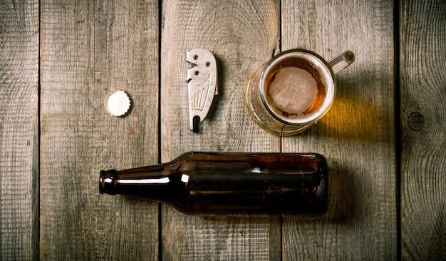 Service à bière: bouteille, verre de bière, un ouvre-bouteille, bouchon sur table en bois.