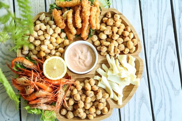 Service à bière avec pois chiches, fromage, dushbara et crevettes