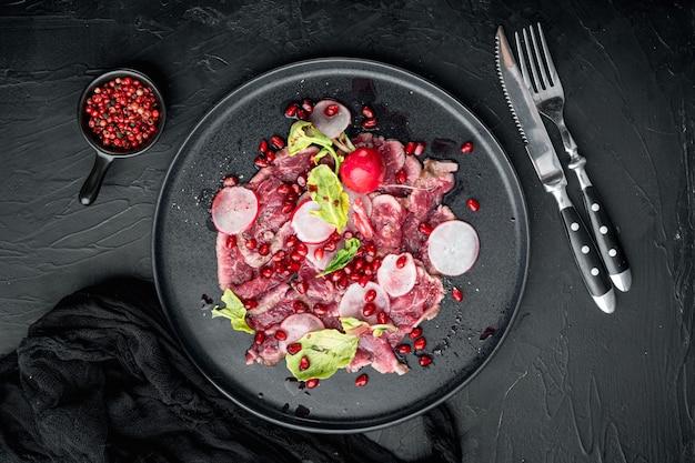 Service de bœuf carpaccio, radis et grenat, sur assiette, sur pierre noire