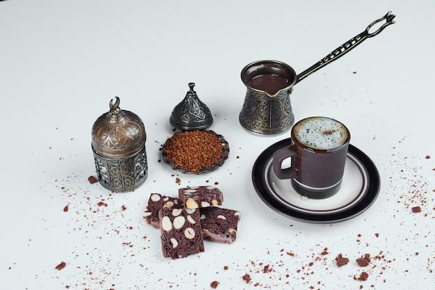 Service à café turc avec des tranches de gâteau au cacao.