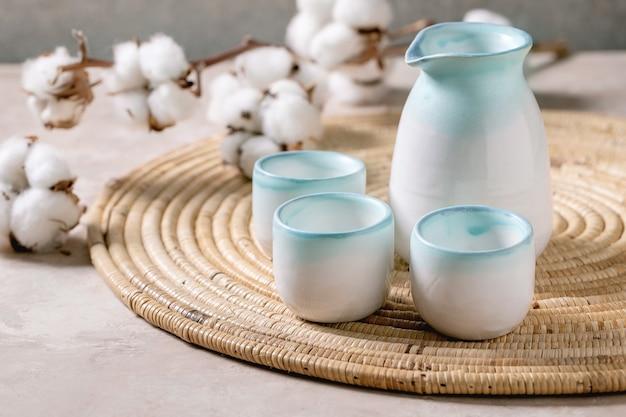 Service en céramique à saké pour japonais traditionnel avec pichet et trois tasses, posé sur une serviette en paille avec des fleurs en coton