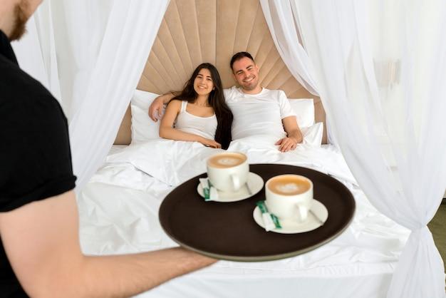 Service de chambre offrant 2 tasses de café dans une chambre d'hôtel pour couple marié allongé dans un lit le matin