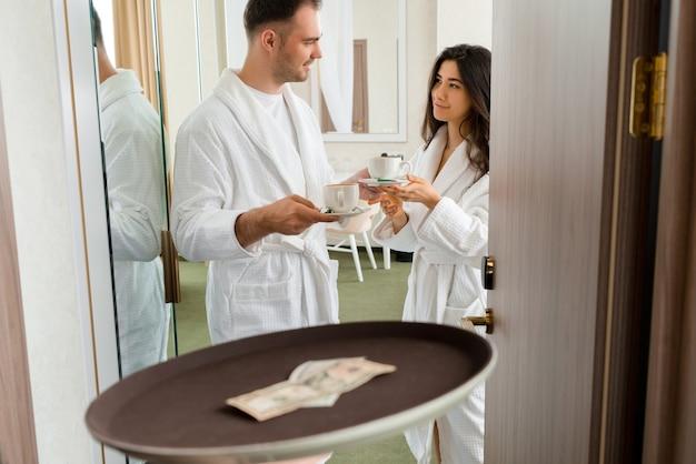 Service de chambre offrant du café dans une chambre d'hôtel pour un couple marié portant un peignoir qui donne des pourboires en dollars