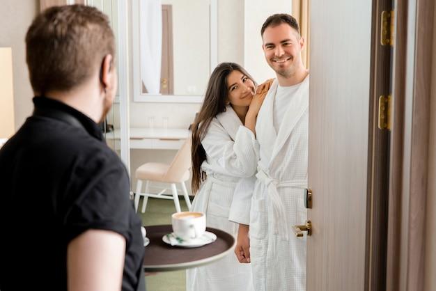 Service de chambre offrant du café dans une chambre d'hôtel pour couple marié portant un peignoir
