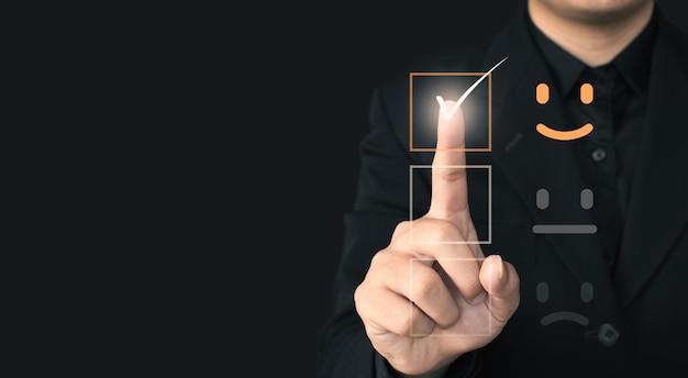 Service client et concept de satisfaction, l'homme d'affaires touche l'écran virtuel sur l'icône heureuse qui montre la satisfaction du client.