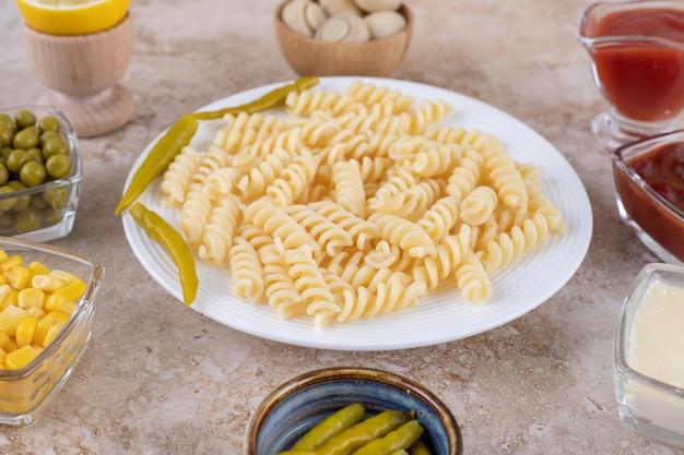 Service de dîner avec plat principal entouré de vinaigrettes et apéritifs sur une surface en marbre