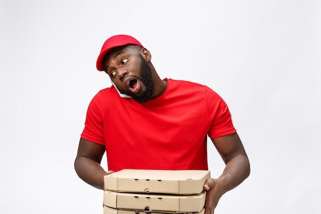 Service de livraison: beau livreur de pizza africaine parlant au mobile avec une expression faciale choquante.