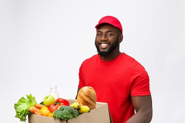 Service de livraison - bel homme de livraison afro-américain transportant une boîte d'emballage de nourriture d'épicerie et de boisson du magasin.